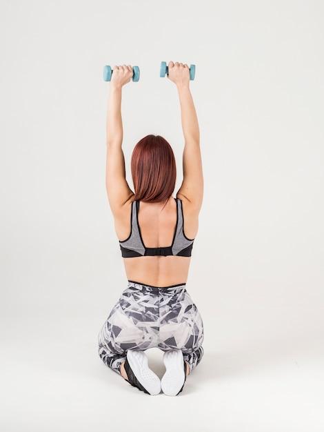 重みを保持している運動の女性の背面図 無料写真