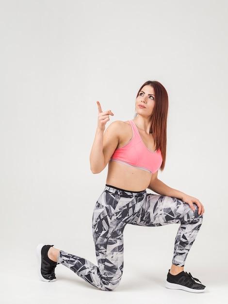 Взгляд со стороны атлетической женщины указывая вверх Бесплатные Фотографии