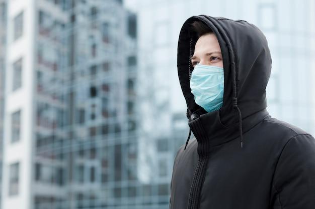医療マスクを身に着けている都市の男の側面図 無料写真