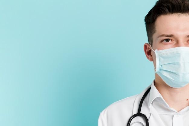 Вид спереди на половину лица врача в медицинской маске Бесплатные Фотографии