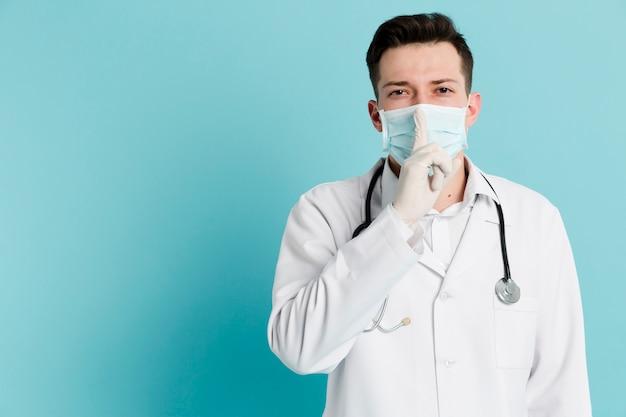 医療マスクと静かなサインを作る手術用手袋を持つ医師の正面図 無料写真