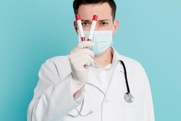 バキュテナーを保持している医療マスクを持つ医師の正面図 無料写真