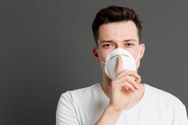 Вид спереди человека, носящего медицинскую маску и делая тихий знак Бесплатные Фотографии