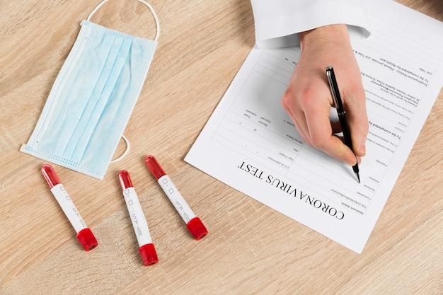 Высокий угол доктора, заполняющего коронавирусный тест Бесплатные Фотографии