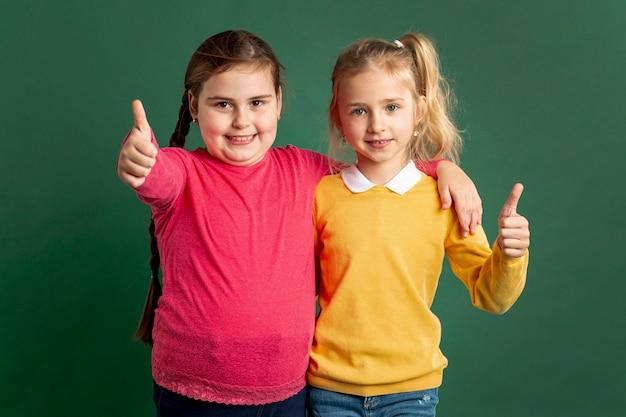 Маленькие девочки показывают знак ок Бесплатные Фотографии