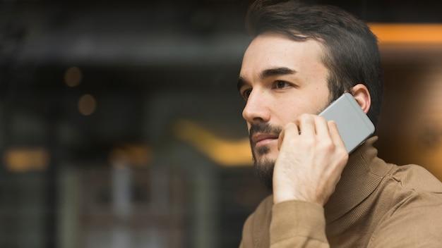 携帯電話で話しているサイドビュービジネス男 無料写真