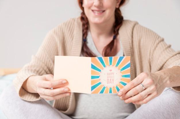 グリーティングカードを読んで妊娠中の女性をクローズアップ 無料写真