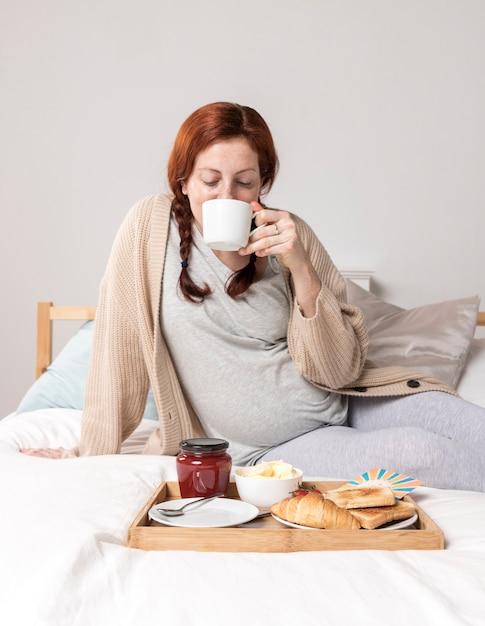 ベッドでブランチを楽しむハイアングル女性 無料写真