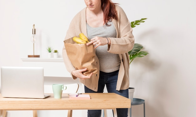 Крупным планом беременная женщина с продуктовой сумкой Бесплатные Фотографии