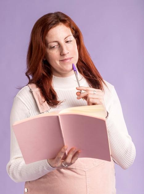 Книга чтения беременной женщины низкого угла Бесплатные Фотографии