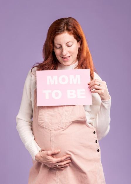Низкий угол беременная женщина, держащая бумагу с мамой, чтобы быть сообщение Бесплатные Фотографии