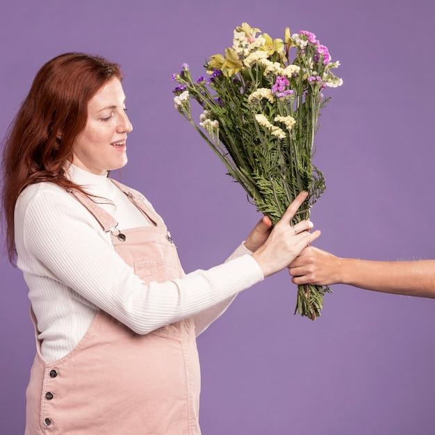 Беременная женщина получает букет цветов Бесплатные Фотографии