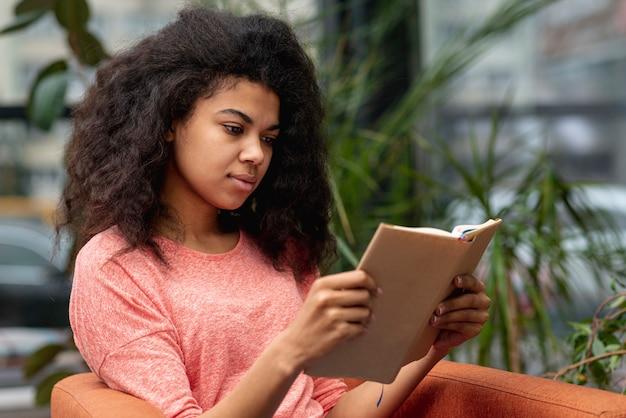 肘掛け椅子の読書の女の子 無料写真
