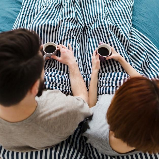 コーヒーのカップを保持しているベッドのカップル 無料写真