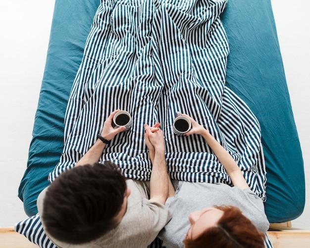 Длинный выстрел людей, сидящих в постели, пьющих кофе Бесплатные Фотографии