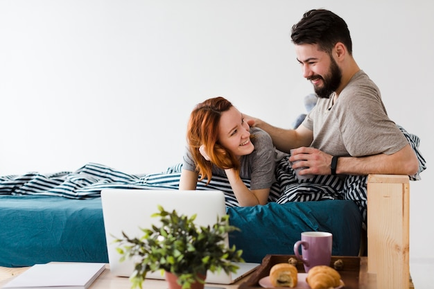 Милая пара смотрит друг на друга и ноутбук Бесплатные Фотографии