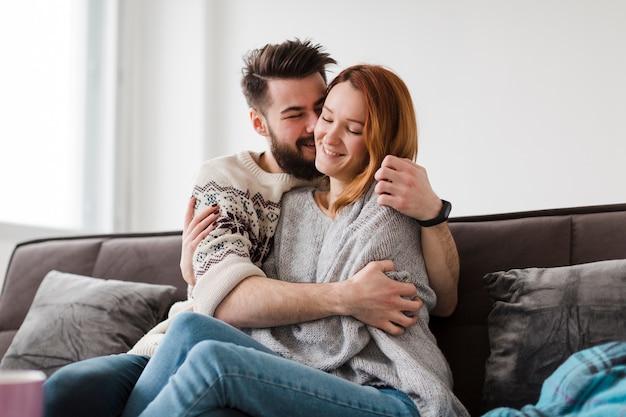 リビングルームで彼のガールフレンドにキスをする男性 無料写真