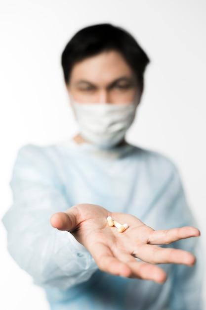 Расфокусированные доктор с медицинской маской, держа в руке таблетки Бесплатные Фотографии