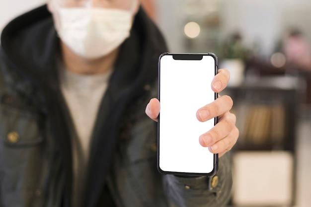 Вид спереди человека с медицинской маской, подняв телефон Бесплатные Фотографии