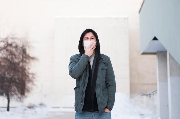 Вид спереди человека с медицинской маской, позируя снаружи Бесплатные Фотографии