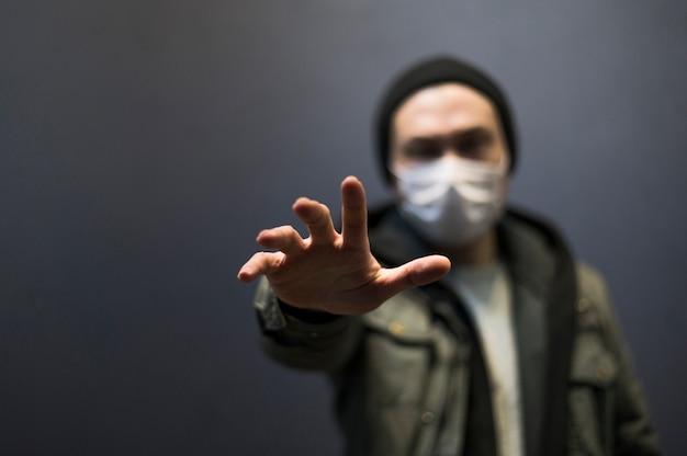 Вид спереди расфокусированным человек с медицинской маской, достигнув кого-то Бесплатные Фотографии