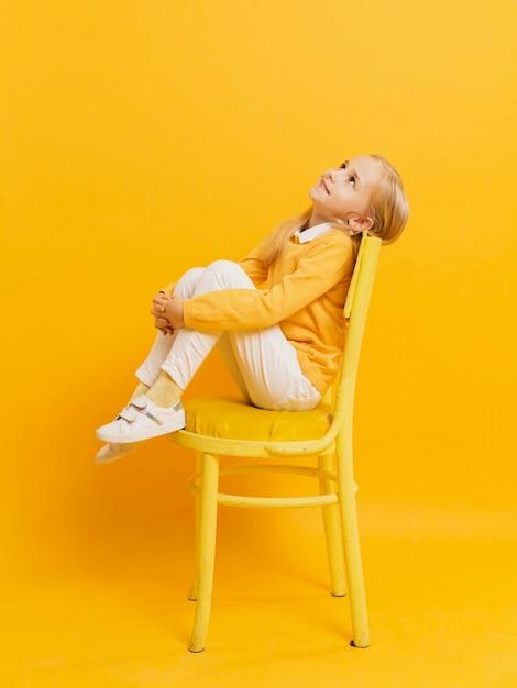 見上げながら椅子でポーズの女の子の側面図 無料写真