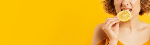 レモンのクローズアップを食べる女性 無料写真