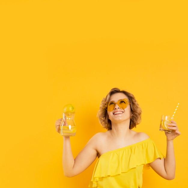 レモネードのガラスを保持しているサングラスをかけたスマイリー女性 無料写真