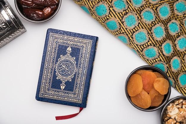 フラット横たわっていたスナックとテーブルの上のコーラン 無料写真