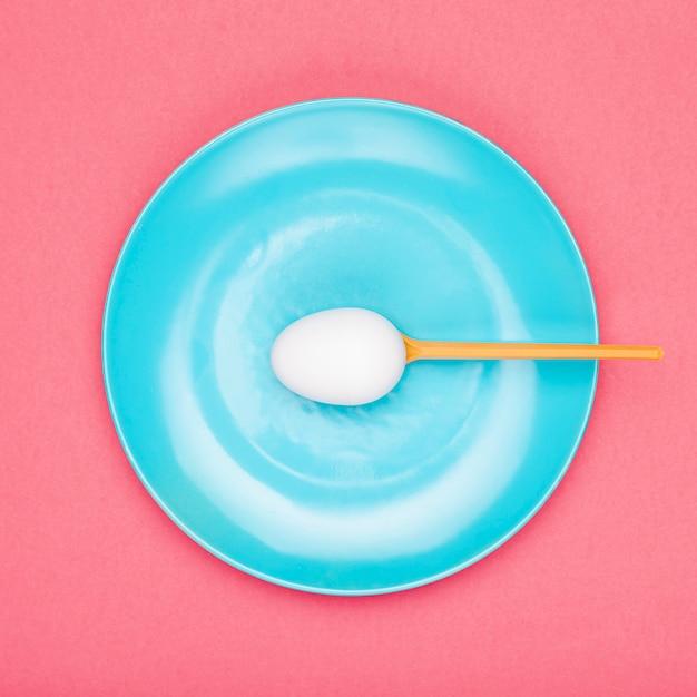 卵を保持しているスプーンでトップビュープレート 無料写真