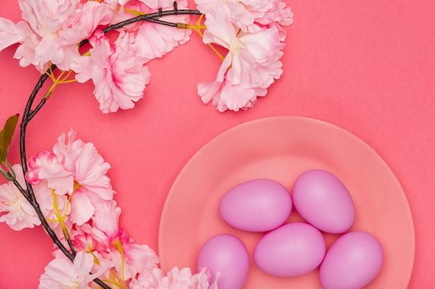 皿の上の花の横に塗られた卵 無料写真