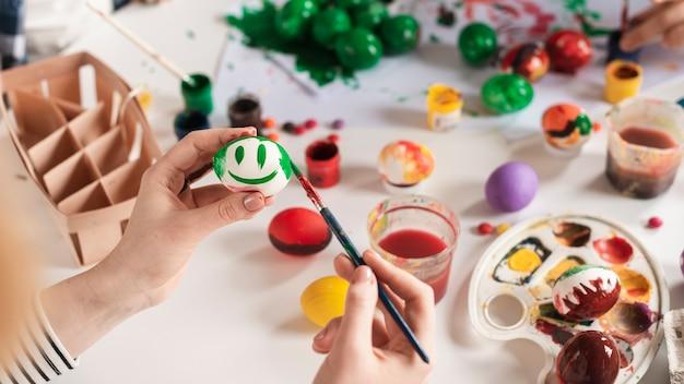 Макро руки рисуют яйцо на пасху Бесплатные Фотографии