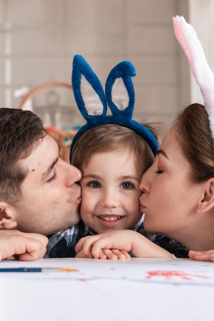 Крупным планом очаровательны ребенка, которого целуют мать и отец Бесплатные Фотографии
