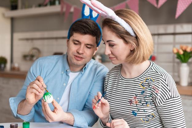 Отец и мать рисуют яйца на пасху Бесплатные Фотографии