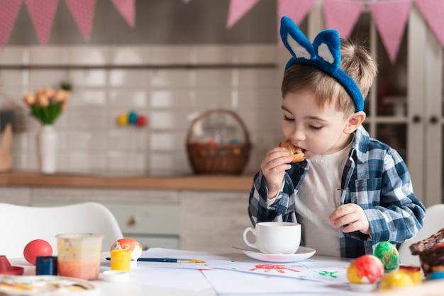 Прелестный маленький ребенок с ушками зайчика ест печенье Бесплатные Фотографии