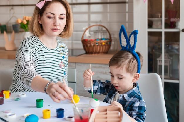 Мать учит маленького мальчика, как рисовать яйца на пасху Бесплатные Фотографии