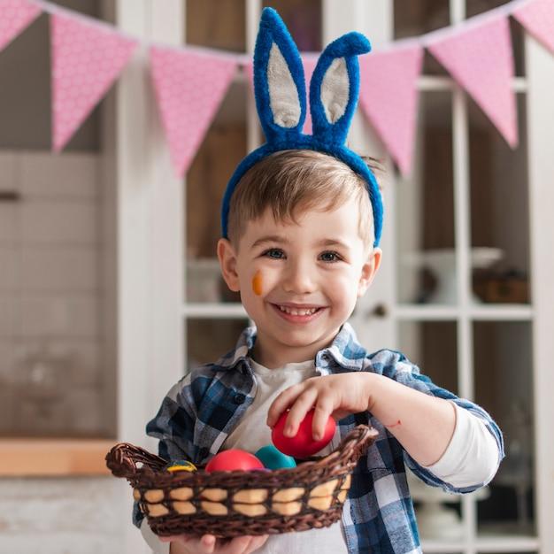 Портрет прелестный маленький мальчик держит корзину с яйцами Бесплатные Фотографии