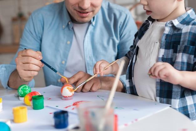 Милый маленький мальчик учится рисовать яйца на пасху Бесплатные Фотографии