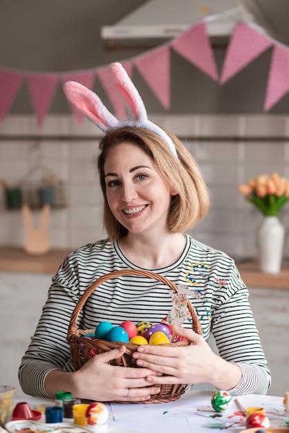 Портрет очаровательны женщина, держащая корзина с пасхальными яйцами Бесплатные Фотографии