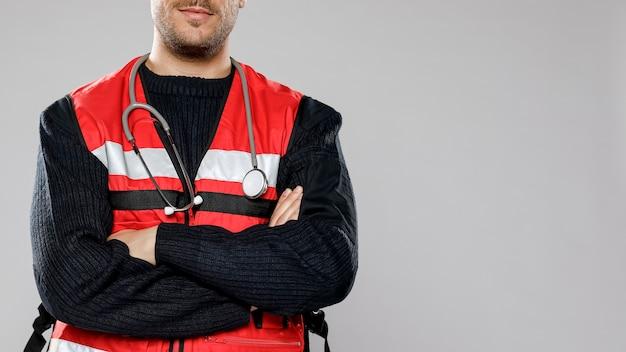 組んだ腕とコピースペースを持つ男性の救急救命士 無料写真