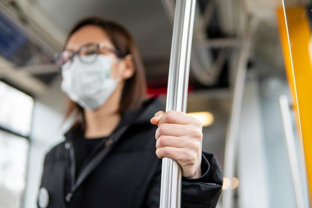 Портрет молодой женщины с помощью общественного транспорта с маской Бесплатные Фотографии