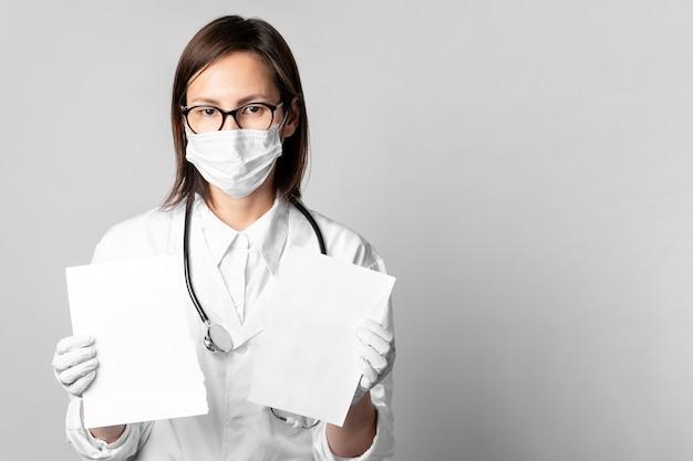 論文を保持しているサージカルマスクを持つ医師の肖像画 無料写真
