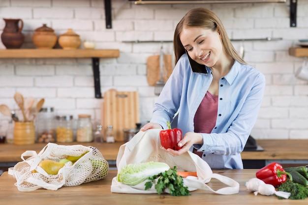 Красивая молодая женщина, принимая продукты из многоразовых сумок Бесплатные Фотографии
