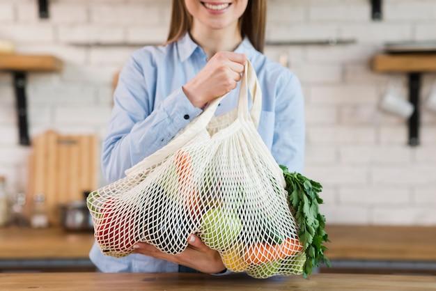 Положительная молодая женщина держа многоразовую сумку с овощами Бесплатные Фотографии