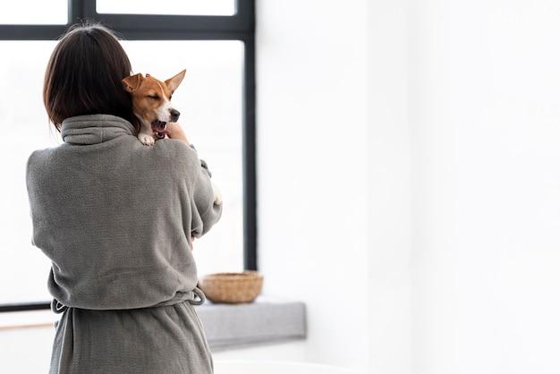 彼女の犬を保持しているバスローブの女性の背面図 無料写真