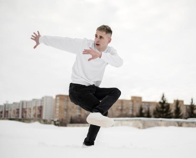 ダンスをしながらポーズをとってヒップホップアーティストの側面図 無料写真