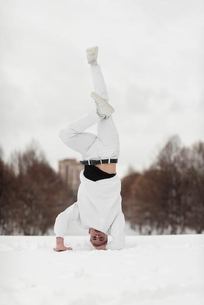 雪の中に頭の上に立っている男性のヒップホップの実行者 無料写真