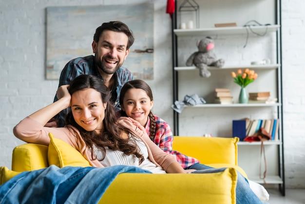 リビングルームのソファに座って幸せな家族 無料写真