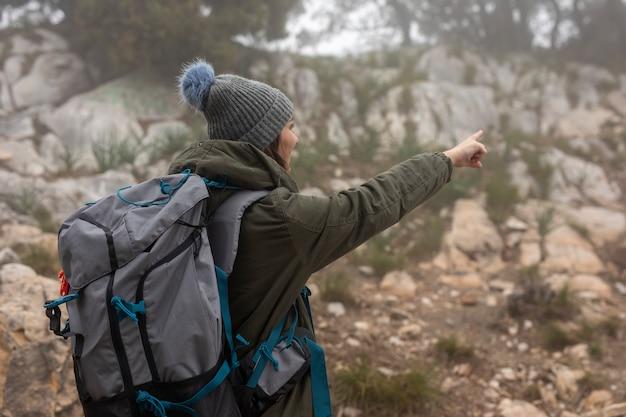 自然の中でバックパックを持つミディアムショット女性 無料写真