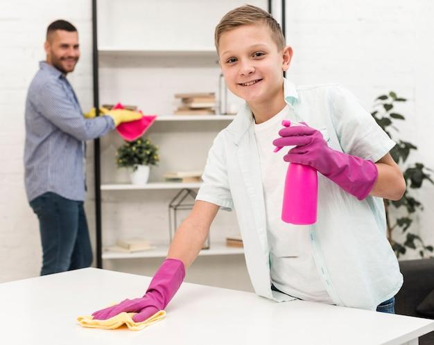 ゴム手袋で掃除しながらポーズをとってスマイリー少年 無料写真